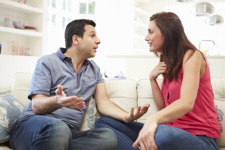 Hispanic Couple Sitting On Sofa Arguing photo