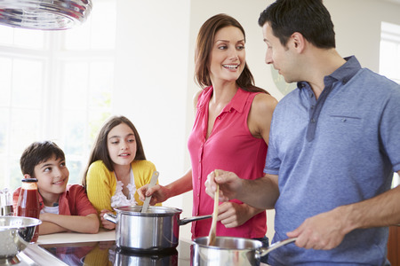 Hispanic Family Cooking Meal At Home Together