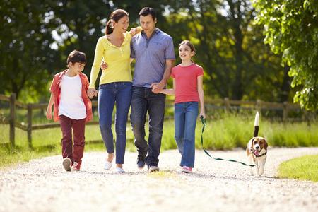 家庭: 西班牙裔家庭以狗走在鄉村