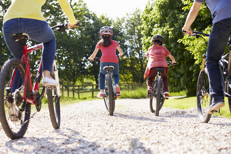 Rear View Of Hispanic Family On Cycle Ride In Countryside Stock Photo