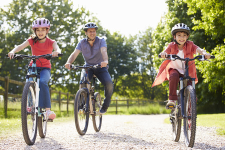 father daughter: Hispanic Father And Children On Cycle Ride In Countryside