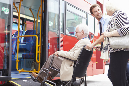 Driver Helping Senior koppel raad Bus Via Rolstoelhelling Stockfoto