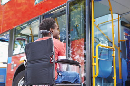 handicapped accessible: Disabled Woman In Wheelchair Boarding Bus Stock Photo