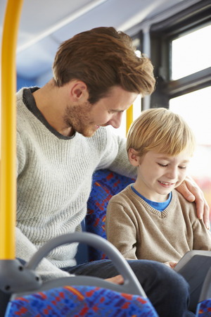 Son Using Digital Tablet On Bus Journey With Father photo