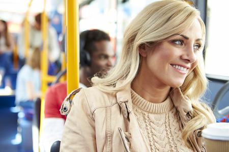 personas sentadas: Mujer que disfruta de la bebida para llevar en el autob�s viaje