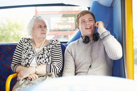 Hombre pasajeros perturbadores en el bus camino con la llamada de teléfono