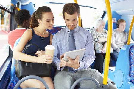 ビジネスマンおよび女性のバス上のデジタル タブレットを使用して