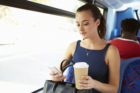 Zakenvrouw verzenden van SMS-bericht op de bus