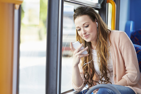 Young Woman Wearing Earphones Listening To Music On Bus photo
