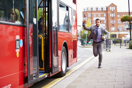 running late: Businessman Running To Catch Bus Stop
