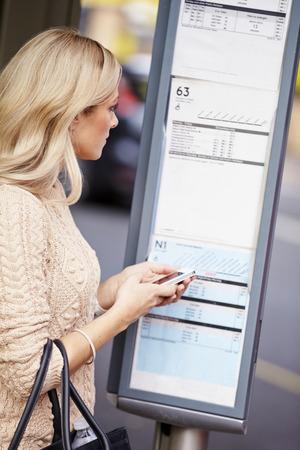 parada de autobus: Mujer en la parada de autob�s con el tel�fono m�vil de lectura Horarios