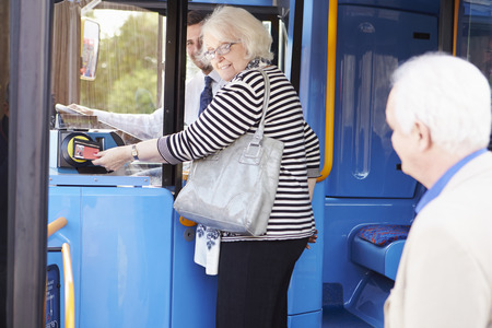 Senior Couple Boarding Bus And Using Pass Stock Photo