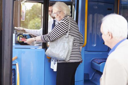 Superior Bus Boarding Pareja Y Usando Pass Foto de archivo