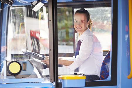 Portrait Of Female Bus Driver Behind Wheel photo