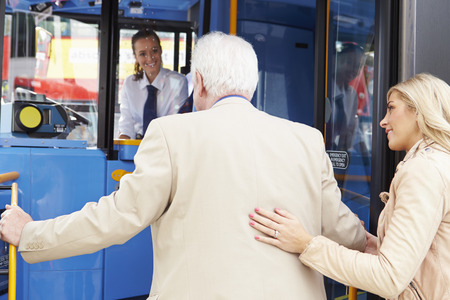 Woman Helping Senior Man To Board Bus Stock Photo