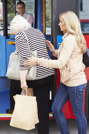 Ayuda de la mujer mayor de la mujer a la Junta de autobuses