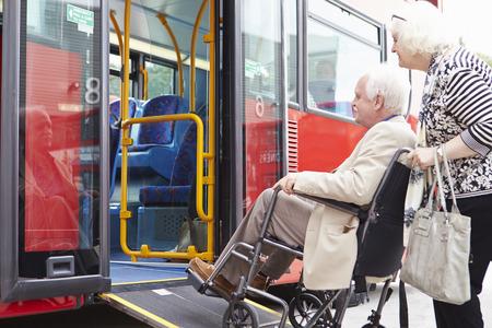 年配のカップル搭乗バス車椅子アクセス ランプを使用して