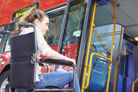 Disabled Woman In Wheelchair Boarding Bus Stock Photo