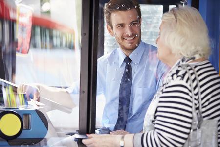 シニアの女性の搭乗バスのチケットを購入