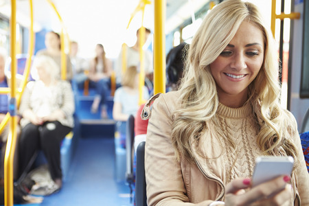 transportations: Woman Reading Text Message On Bus