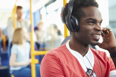 listening to music: El hombre con auriculares escuchan la m�sica en autob�s Viaje Foto de archivo
