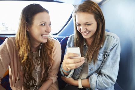 Dos mujeres jóvenes la lectura de mensajes de texto en autobús