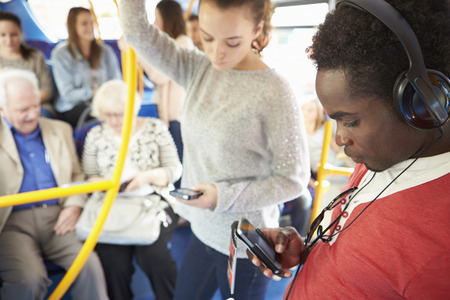 Passengers Using Mobile Devices On Bus Journey