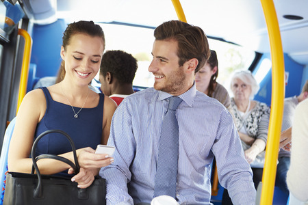 Businessman And Woman Looking At Mobile Phone On Bus photo
