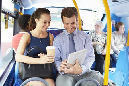 버스에 디지털 태블릿을 사용하여 사업가와 여자