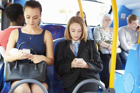 Passengers Sitting On Bus Sending Text Messages Archivio Fotografico