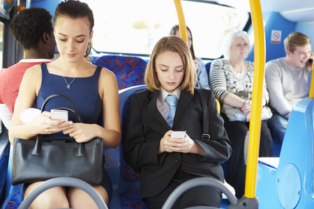 seat: Passengers Sitting On Bus Sending Text Messages Stock Photo