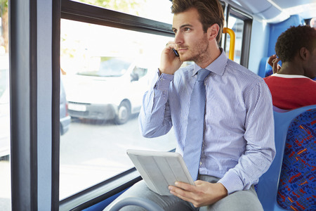 Businessman Using Mobile Phone And Digital Tablet On Bus Фото со стока