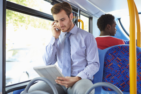 Businessman Using Mobile Phone And Digital Tablet On Bus photo