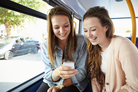 old phone: Two Young Women Reading Text Message On Bus Stock Photo