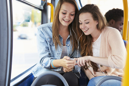 people smile: Two Young Women Listening To Music On Bus
