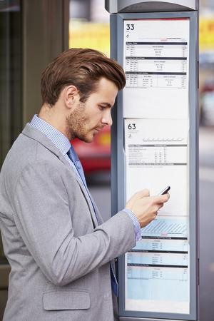 De empresario en la parada de autobús con el teléfono móvil de lectura Horarios