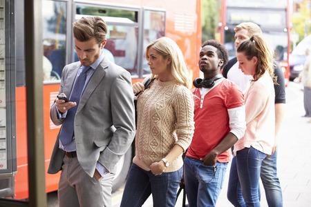 parada de autobus: Cola de gente esperando en la parada Foto de archivo