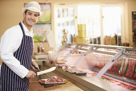 Butcher Preparing Meat In Shop Banque d'images