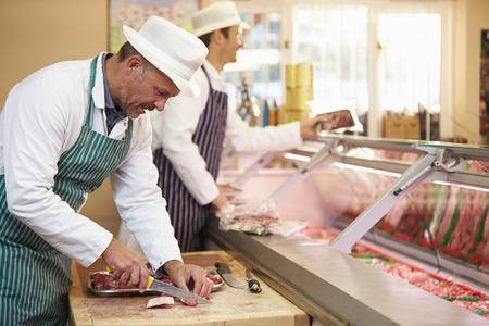 meat counter: Two Butchers Preparing Meat In Shop