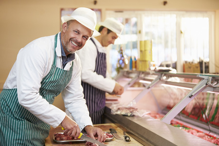 bacon portrait: Two Butchers Preparing Meat In Shop