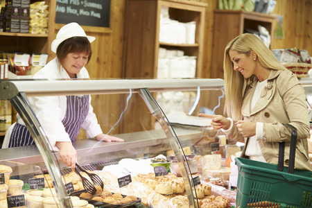 Female Sales Assistant Serving Customer In Delicatessen photo