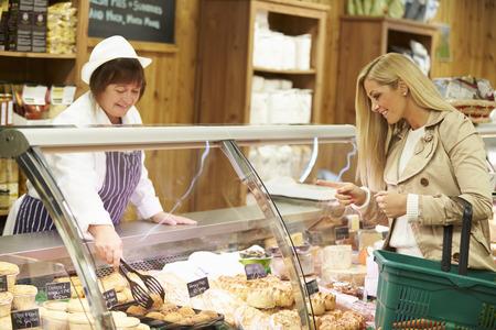 Female Sales Assistant Serving Customer In Delicatessen