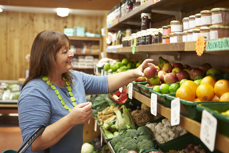 farm shop: Female Customer At Vegetable Counter Of Farm Shop Stock Photo