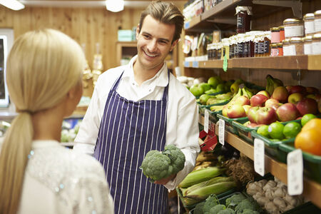 farm shop: Assistant Helping Customer At Vegetable Counter Of Farm Shop