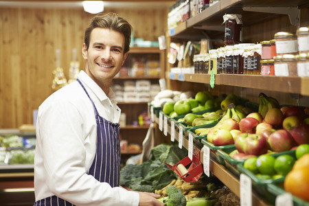 farm shop: Male Sales Assistant At Vegetable Counter Of Farm Shop Stock Photo