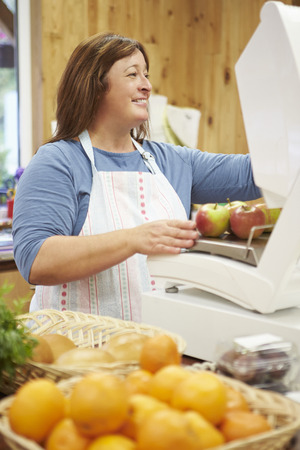 farm shop: Female Sales Assistant At Checkout Of Farm Shop