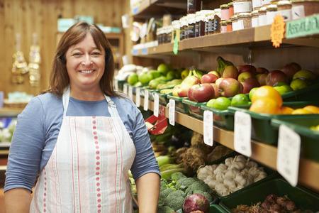 farm shop: Female Sales Assistant At Vegetable Counter Of Farm Shop