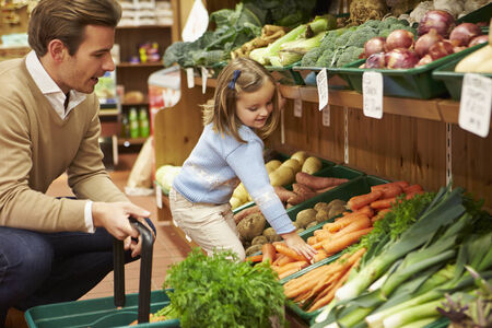 farm shop: Father And Daughter Choosing Fresh Vegetables In Farm Shop