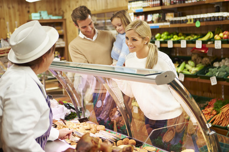 Female Sales Assistant Serving Family In Delicatessen photo