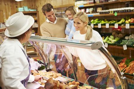 Deli: Female Sales Assistant Serving Family In Delicatessen